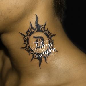 太陽とイニシャルのタトゥー