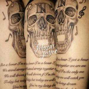 スカルとメッセージのタトゥー