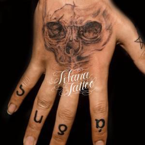 スカルと文字のタトゥー